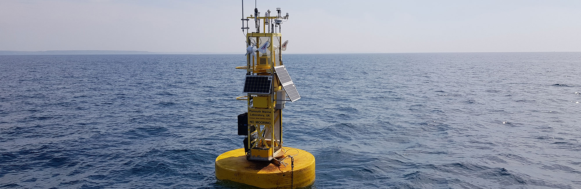 Picture of a yellow scientific data buoy at sea